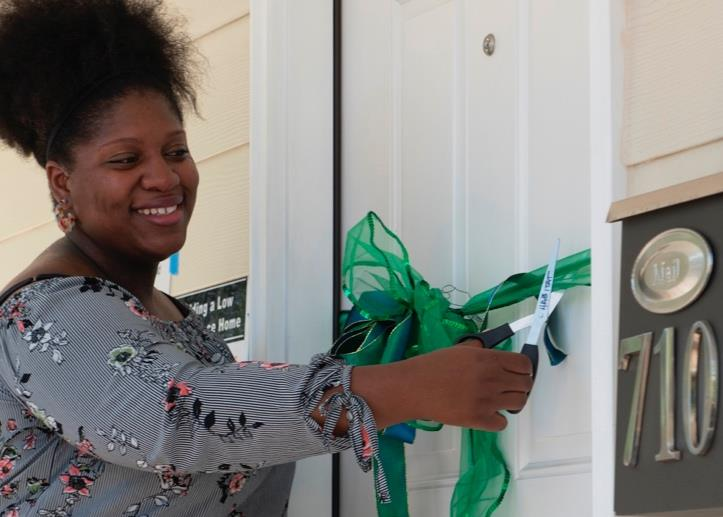 Tanae Lawal cutting the ribbon on the door to her new home in Cambridge