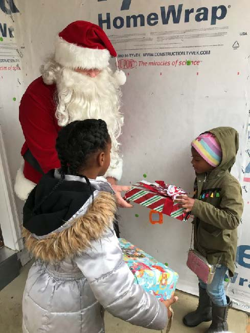 Santa stopped by one of the Habitat homes still under construction on Brooks Lane on December 14th to deliver presents to the children of Habitat homebuyers.
